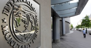 Pedestrians walk past the International Monetary Fund headquarters' complex in Washington Sunday, May 2, 2010. A senior International Monetary Fund official says the IMF's executive board is meeting in Washington to consider how much aid to grant Athens under a massive rescue loan package.
