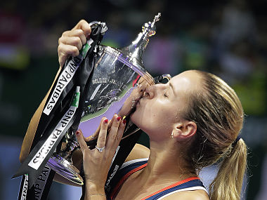 Dominika Cibulkova of Slovakia kisses her trophy after beating Angelique Kerber of Germany in their women's singles final match at the WTA tennis tournament in Singapore, Sunday, Oct. 30, 2016. (AP Photo/Wong Maye-E)