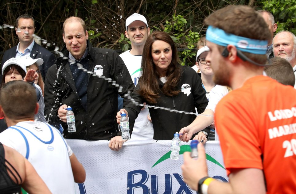 TOPSHOT - A runner squirts water towards Britain's Prince William, Duke of Cambridge and Britain's Catherine, Duchess of Cambridge as they hand out water to runners during the 2017 London Marathon in London on April 23, 2017. / AFP PHOTO / POOL / Chris JacksonCHRIS JACKSON/AFP/Getty Images