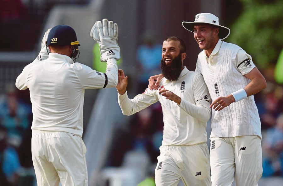 England player Moeen Ali (C) celebrates the dismissal of South Africa's batsman Theunis de Bruyn with Stuart Broad (R) on day 4 of the fourth Test match between England and South Africa at Old Trafford cricket ground in Manchester on August 7, 2017. / AFP PHOTO / OLI SCARFF / RESTRICTED TO EDITORIAL USE. NO ASSOCIATION WITH DIRECT COMPETITOR OF SPONSOR, PARTNER, OR SUPPLIER OF THE ECB