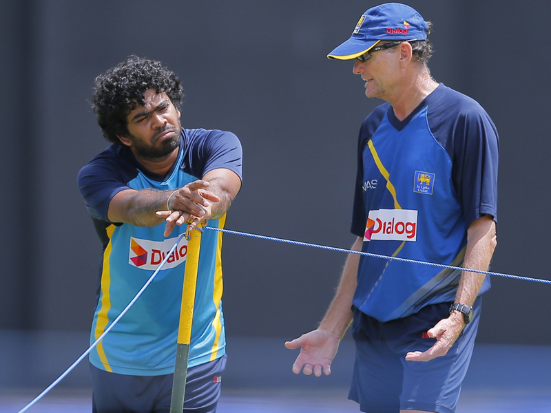 Sri Lankan cricketer Lasith Malinga, left and coach Graham Ford chat during a practice session ahead of the second Twenty20 cricket match against Australia in Colombo, Sri Lanka, Thursday, Sept. 8, 2016. (AP Photo/Eranga Jayawardena)
