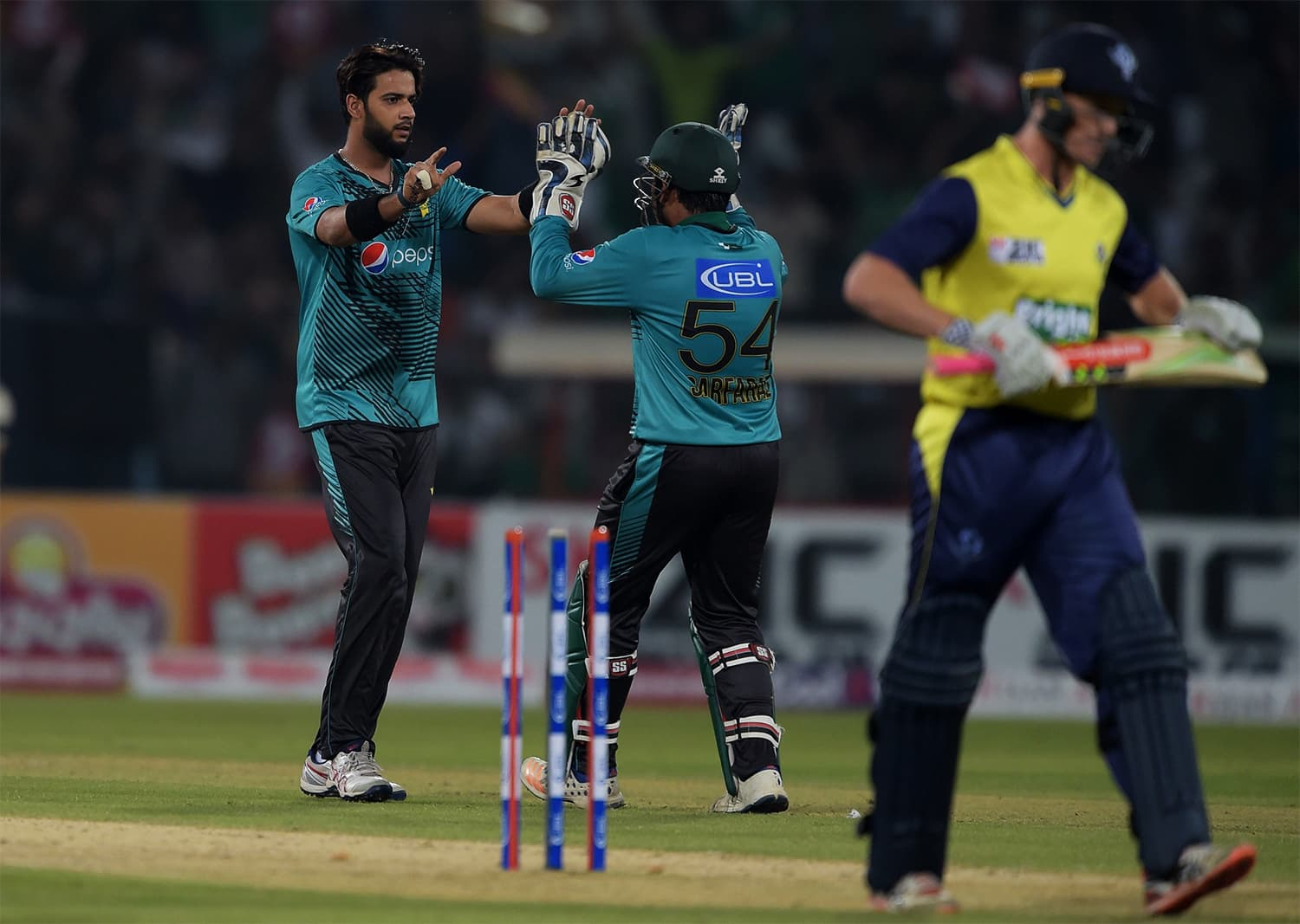 Pakistani spinner Imad Wasim (L) celebrates with captain and wicketkeeper Sarfraz Ahmad (C) after taking the wicket of World XI batsman George Bailey (R) during the third and final Twenty20 International match between the World XI and Pakistan at the Gaddafi Cricket Stadium in Lahore on September 15, 2017.  / AFP PHOTO / AAMIR QURESHI
