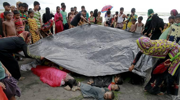 In this Thursday, Aug. 31, 2017, file photo, Bangladeshi villagers cover bodies of Rohingya women and children at Shah Porir Deep, in Teknak, Bangladesh. Three boats carrying ethnic Rohingya fleeing violence in Myanmar have capsized in Bangladesh and over two dozen bodies of women and children have been recovered, officials said Thursday. (AP Photo/Suvra Kanti Das, File)
