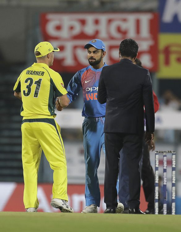 Australian cricket captain David Warner, left, shakes hand with Indian cricket captain Virat Kohli after winning the toss and electing to field during second Twenty20 cricket match in Gauhati, India, Tuesday, Oct. 10, 2017. (AP Photo/Manish Swarup)