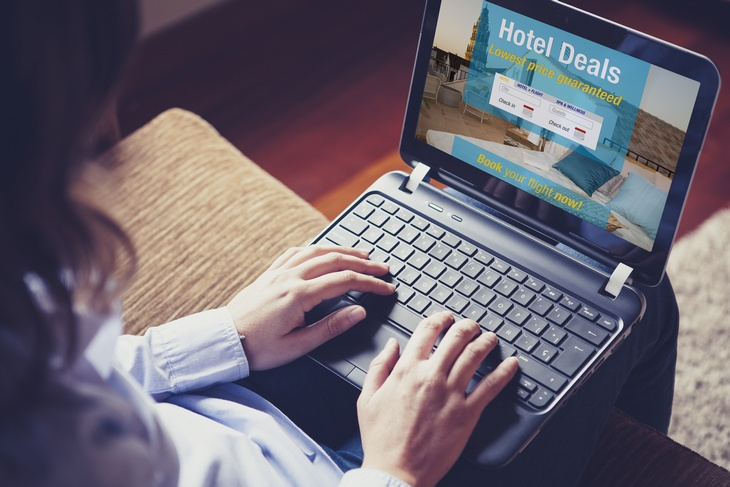 Woman searching a hotel for vacation. Booking template designed on the screen.