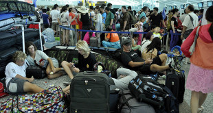 International passengers (foreground) wait with their luggage as others (background) crowd the check-in counters at Ngurah Rai International airport in Kuta, Indonesia's resort island of Bali, on July 11, 2015. Holidaymakers stranded for days in Bali when a volcanic ash cloud forced the closure of the island's main airport began checking in for flights July 11 after Indonesian authorities reopened the terminal. AFP PHOTO / RIYANTO