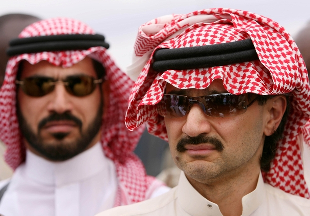 Saudi Prince Al-Walid bin Talal talks to reporters at a food distribution point in Shaba