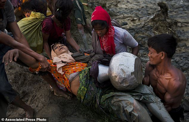 Rohingya Muslims help another after crossing the Naf river near Palong Khali, Bangladesh, Wednesday, Nov. 1 2017. In a scene that's played out over and over again, at least 2,000 exhausted and starving Rohingya crossed the swollen Naf river on Wednesday and waited along the Bangladesh border for permission to cross, fleeing persecution in Myanmar. (AP Photo/Bernat Armangue)
