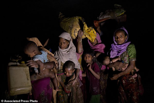 Rohingya women carry children and belongings and walk after having just crossed the Naf river near Palong Khali, Bangladesh, Wednesday, Nov. 1 2017. On Wednesday at least 2,000 exhausted and starving people waited in rice paddy fields at one border crossing for Bangladesh's border guards to let them enter. It's a scene that's played out over and over again with heartbeaking regularity as hundreds of thousands of Rohingya Muslims have fled persecution in Myanmar and escaped to neighboring Bangladesh. (AP Photo/Bernat Armangue)