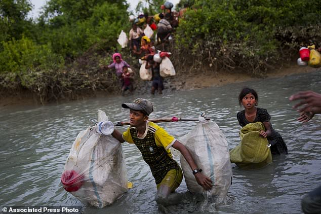 Rohingya Muslims carry their belongings and cross the border from Myanmar into Bangladesh, near Palong Khali, Bangladesh, Wednesday, Nov. 1, 2017. The exodus of Rohingya Muslims, long persecuted in Myanmar, started Aug. 25 when a group of insurgents attacked dozens of police posts. The retribution from Myanmar's authorities was swift and brutal. The violence, which the UN describes as ethnic cleansing, has pushed more than 600,000 Rohingya towards Bangladesh. (AP Photo/Bernat Armangue)