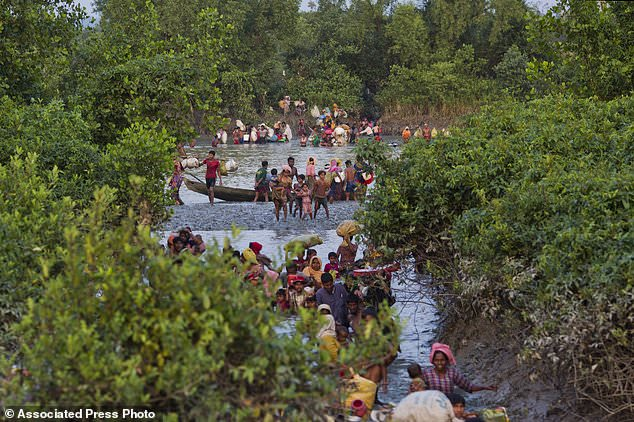 Groups of Rohingya Muslims cross the Naf river at the border between Myanmar and Bangladesh, near Palong Khali, Bangladesh, Wednesday, Nov. 1 2017. On Wednesday at least 2,000 exhausted and starving Rohingya crossed the swollen Naf river and waited along the border for permission to cross. It's a scene that's played out over and over again with heartbeaking regularity as hundreds of thousands of Rohingya Muslims have fled persecution in Myanmar and escaped to neighboring Bangladesh. (AP Photo/Bernat Armangue)