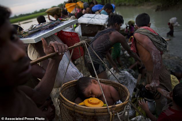 A Rohingya child sleeps inside a basket in which he was carried as a group of Rohingya fled Myanmar into Bangladesh, near Palong Khali, Bangladesh, Wednesday, Nov. 1, 2017. In a scene that's played out over and over again, at least 2,000 exhausted and starving Rohingya crossed the swollen Naf river on Wednesday and waited along the Bangladesh border for permission to cross, fleeing persecution in Myanmar. (AP Photo/Bernat Armangue)