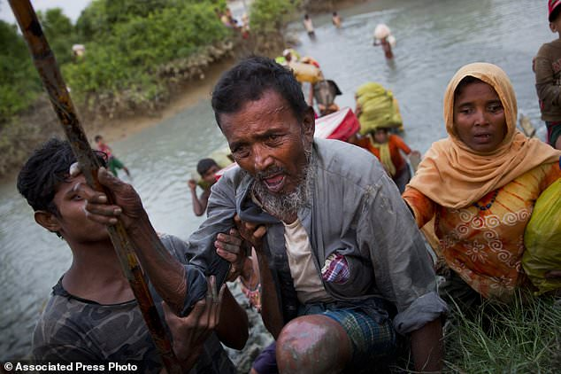 A Rohingya Muslim helps an elderly as they cross over from Myanmar into Bangladesh, near Palong Khali, Bangladesh, Wednesday, Nov. 1, 2017. The exodus of Rohingya Muslims, long persecuted in Myanmar, started Aug. 25 when a group of insurgents attacked dozens of police posts. The retribution from Myanmar's authorities was swift and brutal. The violence, which the UN describes as ethnic cleansing, has pushed more than 600,000 Rohingya towards Bangladesh. (AP Photo/Bernat Armangue)