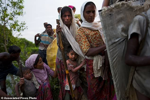 Rohingya Muslim children stay close to elders as they cross the border from Myanmar into Bangladesh, near Palong Khali, Bangladesh, Wednesday, Nov. 1, 2017. In a scene that's played out over and over again, at least 2,000 exhausted and starving Rohingya crossed the swollen Naf river on Wednesday and waited along the Bangladesh border for permission to cross, fleeing persecution in Myanmar. (AP Photo/Bernat Armangue)