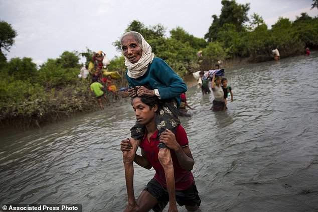 A Rohingya Muslim carries an elderly woman through water after crossing the border from Myanmar into Bangladesh, near Palong Khali, Bangladesh, Wednesday, Nov. 1, 2017. In a scene that's played out over and over again, at least 2,000 exhausted and starving Rohingya crossed the swollen Naf river on Wednesday and waited along the Bangladesh border for permission to cross, fleeing persecution in Myanmar. (AP Photo/Bernat Armangue)