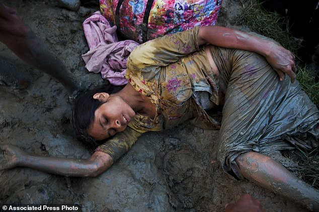 An exhausted Rohingya lies on the muddy ground after crossing over from the Myanmar border into Bangladesh, near Palong Khali, Bangladesh, Wednesday, Nov. 1 2017. In a scene that's played out over and over again, at least 2,000 exhausted and starving Rohingya crossed the swollen Naf river on Wednesday and waited along the Bangladesh border for permission to cross, fleeing persecution in Myanmar. (AP Photo/Bernat Armangue)