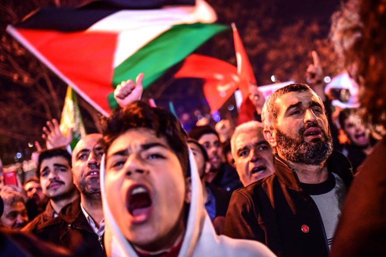Protesters chant slogans and wave Palestinian flags during a demonstration against the US and Israel in front of the US consulate in Istanbul on December 6, 2017. Hundreds of people staged a protest outside the US consulate in Istanbul angrily denouncing the US president's move to recognise Jerusalem as the capital of Israel. Around 1,500 people gathered outside the well-protected compound close to the Bosphorus which was sealed off by police with barricades, an AFP correspondent said. / AFP PHOTO / OZAN KOSEOZAN KOSE/AFP/Getty Images
