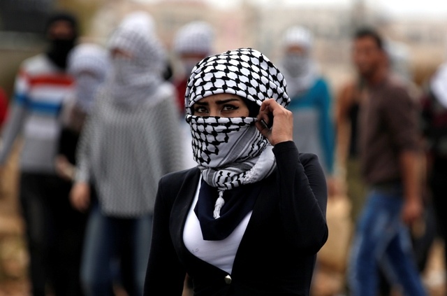 A Palestinian young woman from the Birzeit University looks on during clashes with Israeli security forces in Beit El, on the outskirts of the West Bank city of Ramallah, on October 7, 2015. New violence rocked Israel and the Israeli-occupied West Bank, including a stabbing in annexed east Jerusalem, even as Israel and Palestinian president Mahmud Abbas took steps to ease tensions. AFP PHOTO / ABBAS MOMANI