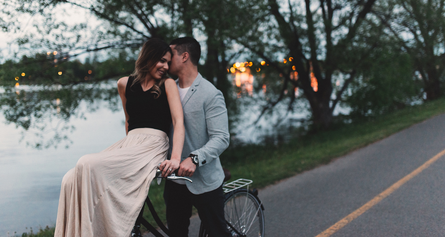 Romantic young man whispering to girlfriend on bicycle handlebars by lake at dusk